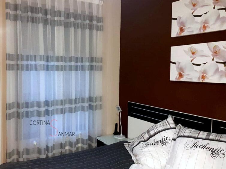 Dormitorio con visillo de rayas horizontales