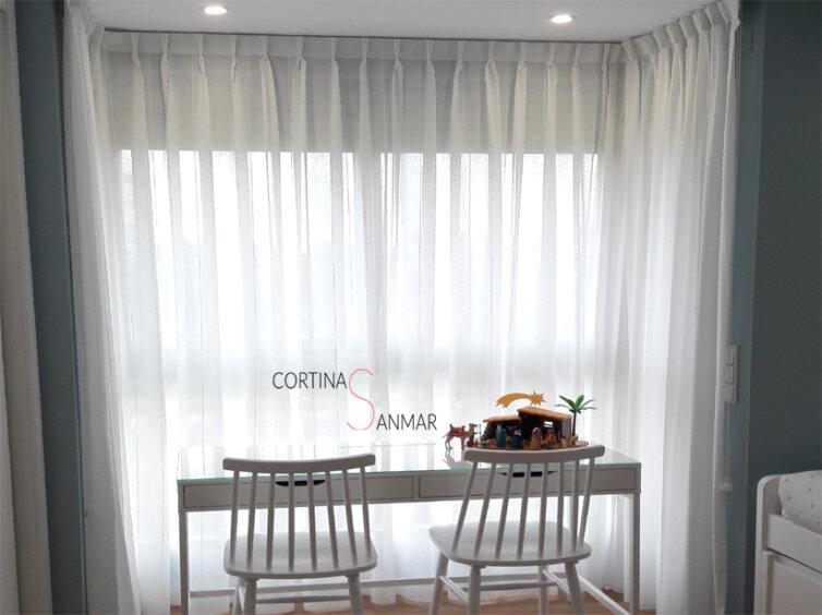 Luz natural para este dormitorio con unos visillos blancos.